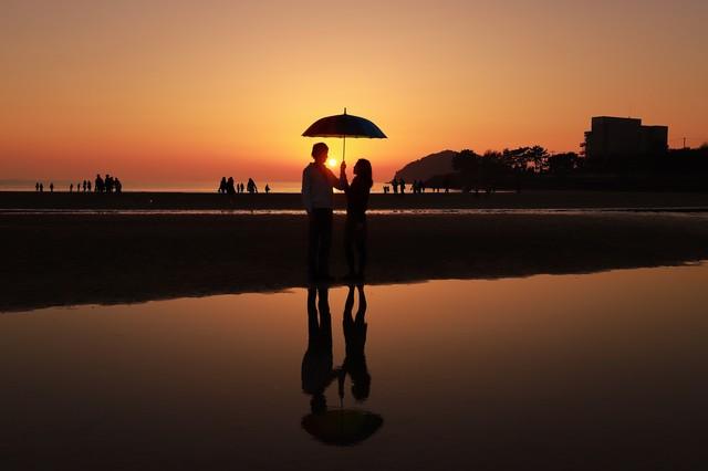 夕暮れの浜辺で相合い傘