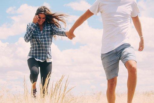 手を繋いで草むらを歩く男女