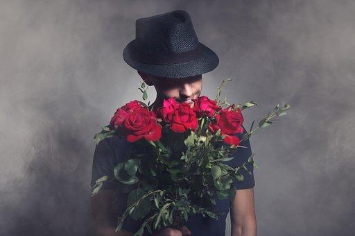 赤い薔薇を持った男性
