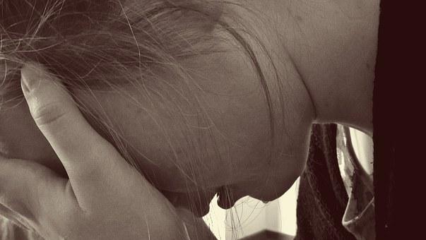 悲しみで顔を覆う女性