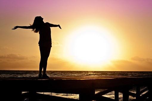 海辺で両手を広げる女の子