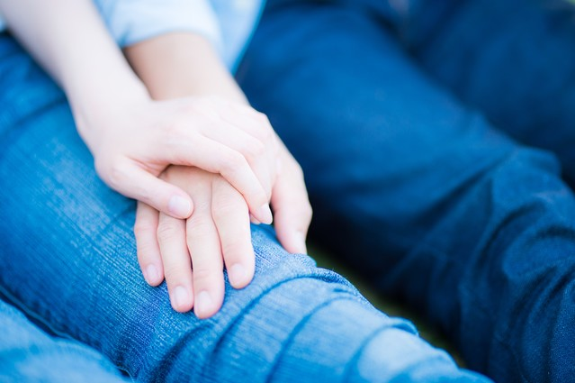 膝の上で手を重ねる男女