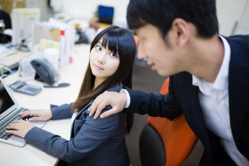 女性の肩を触る男性