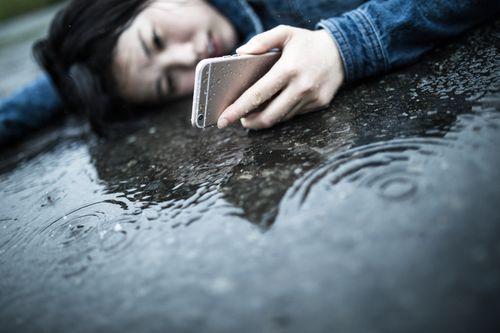 雨の中道路に寝転がる女性