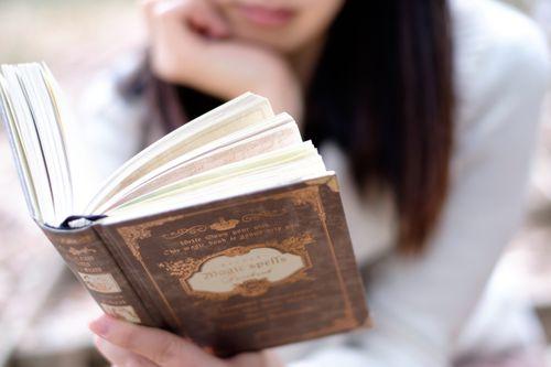 洋書をカ片手に時間を潰している女性