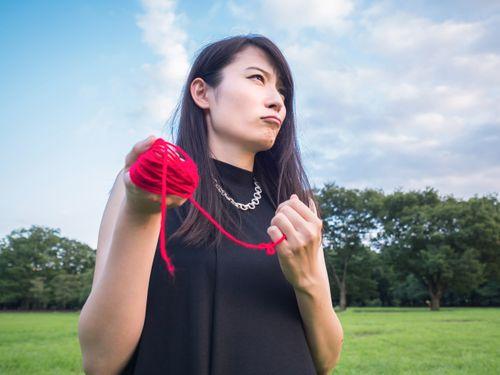 赤い糸を持った悔しそうな女性
