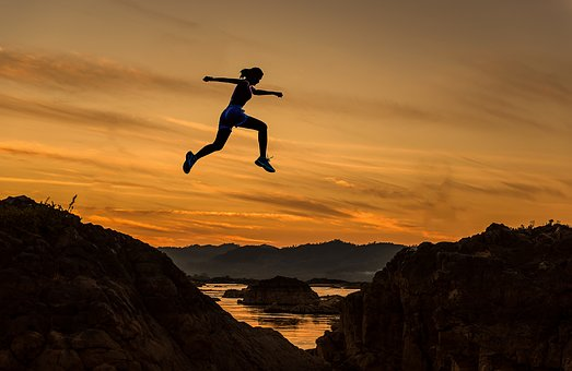 飛び越える女性のシルエット